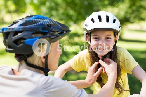 Mother attaching her daughters cycling helmet
