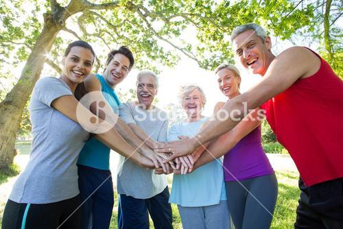 Happy athletic group putting their hands together