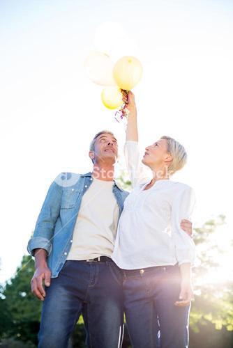Cute couple holding up balloons at the park