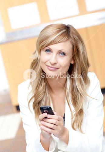 Radiant businesswoman sending a text message with her cellphone