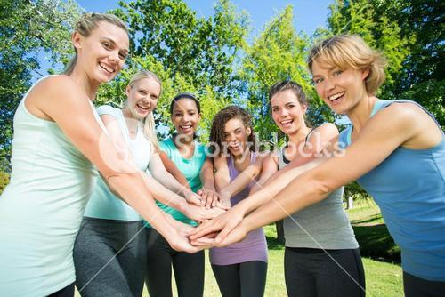 Fitness group putting hands together