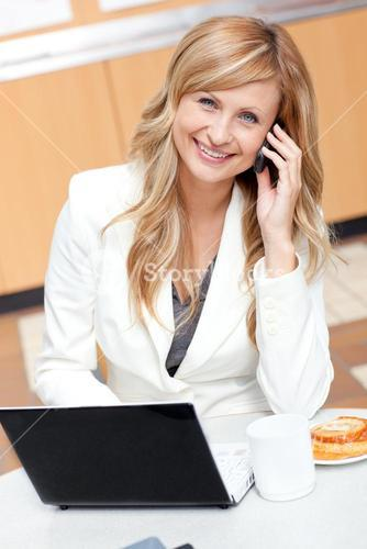 Radiant businesswoman with laptop, coffee and food talking on phone