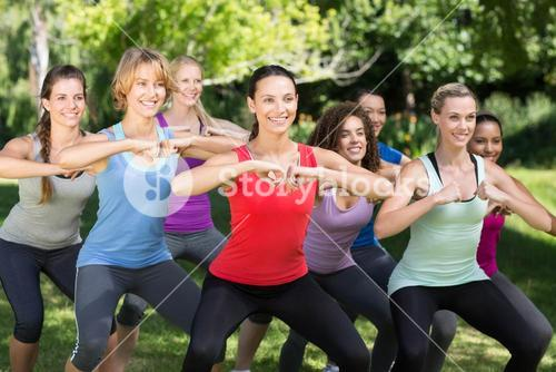 Fitness group squatting in park