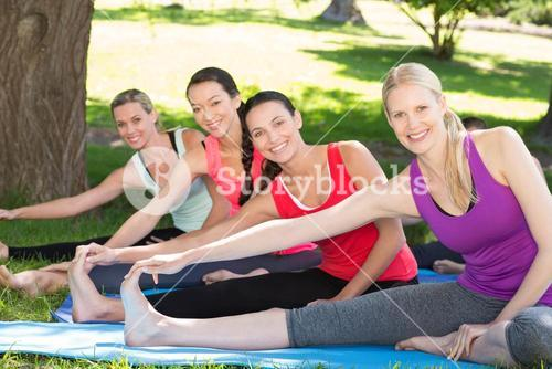 Fitness group doing yoga in park
