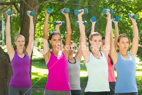 Fitness group lifting hand weights in park
