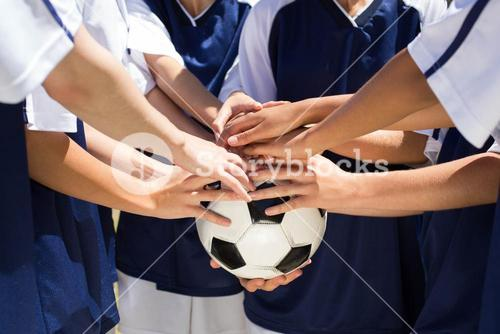 Pretty football players putting hands together