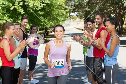 Runners applauding a racer in the park