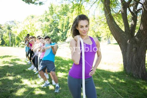 Fitness group playing tug of war