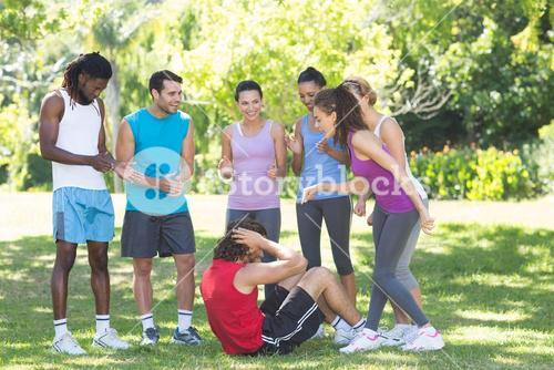 Fitness group encouraging man doing sit ups