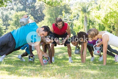 Fitness group planking in park with coach