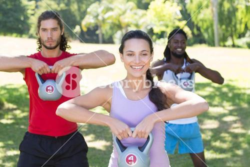 Fitness group working out in park with kettle bells