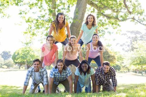 Happy friends in the park making human pyramid