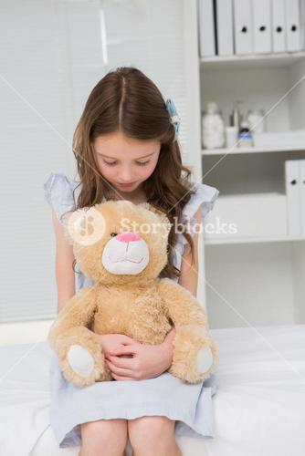 Little girl with her teddy bear in her harms