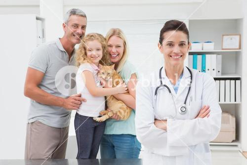 Veterinarian and cat owners smiling at camera