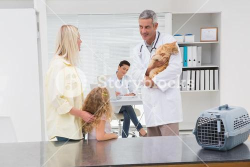 Veterinarian holding cat with its owners