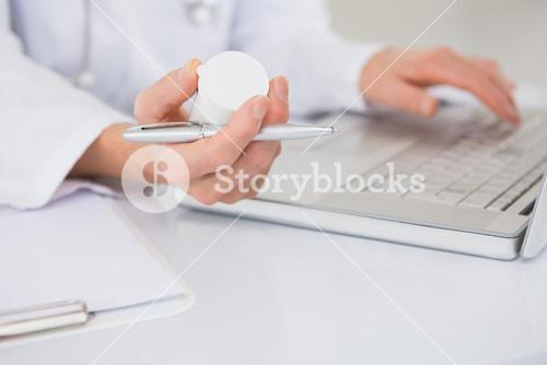Veterinarian typing on keyboard the prescriptions