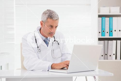 Serious doctor using laptop