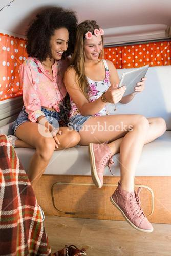 Happy friends on a road trip using tablet