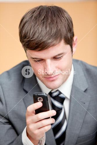 Selfassured businessman writing a text message with his mobile phone