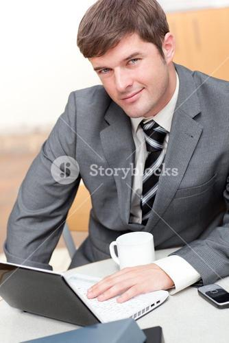 Busy businessman with a laptop, a cellphone and a mug sitting at his desk