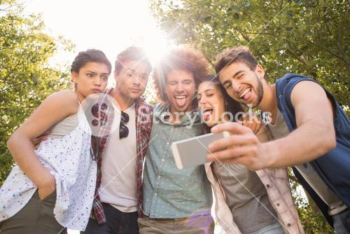 Happy friends in the park taking selfie