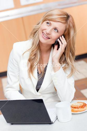 Delighted businesswoman with laptop, coffee and food talking on phone