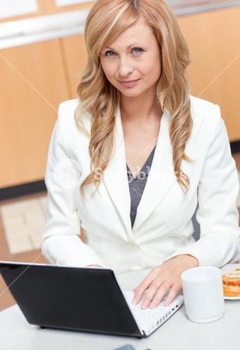 Attractive businesswoman using her laptop with a mug and food in her office