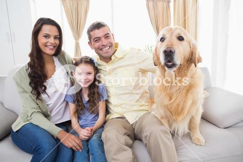 Family sitting with dog on sofa