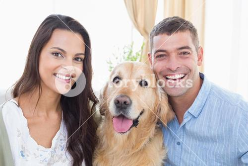 Happy couple with dog at home