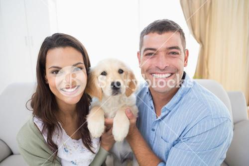 Happy couple holding puppy at home