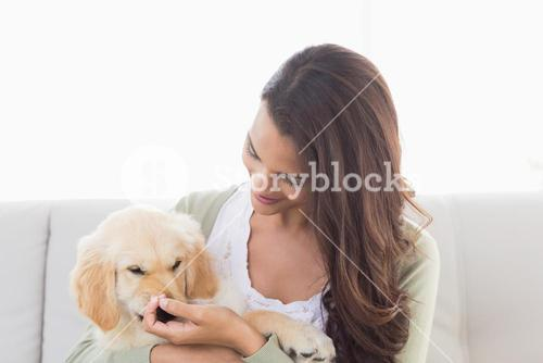 Happy woman playing with puppy