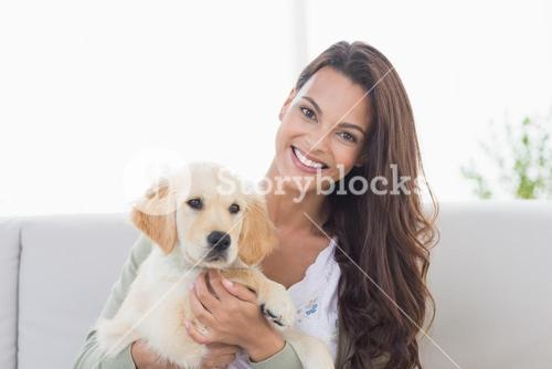 Happy young woman playing with puppy