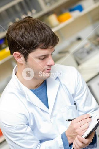 Concentrated scientist writing on a clipboard
