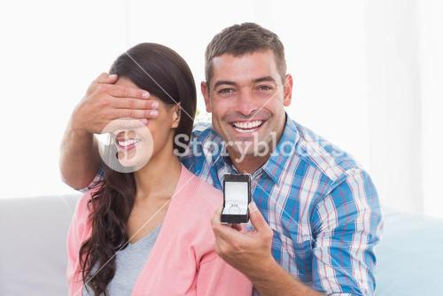 Happy man covering womans eyes while gifting ring