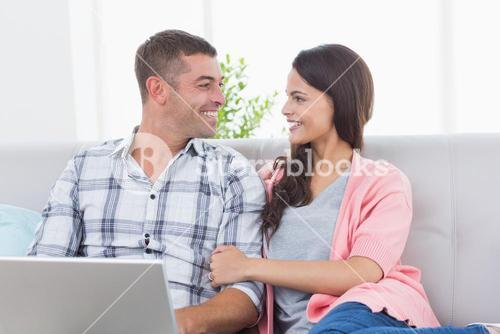 Couple looking at each other while using laptop