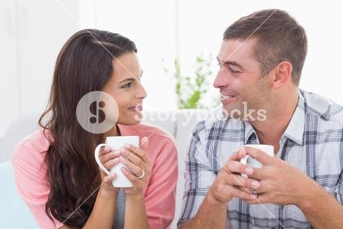 Couple looking at each other while having coffee