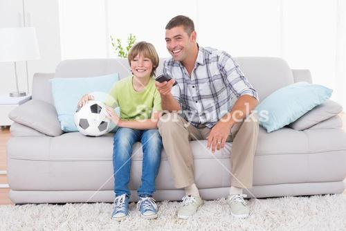 Father and son watching soccer match on sofa