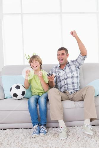 Father and son celebrating success while watching soccer match