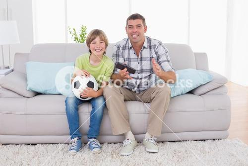Happy boy watching soccer match with father on sofa
