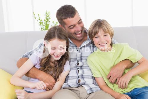 Father tickling children while sitting on sofa