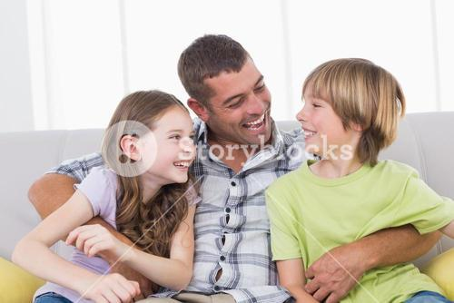 Father tickling son and daughter while sitting on sofa