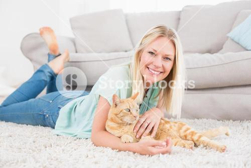 Happy woman with cat lying on rug