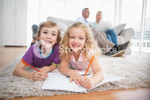 Children drawing on papers while parents sitting on sofa
