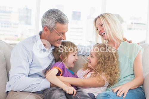 Parents looking at children hugging at home