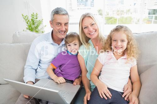 Parents and children with laptop sitting on sofa