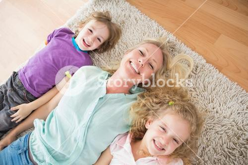 Happy mother and children lying on rug