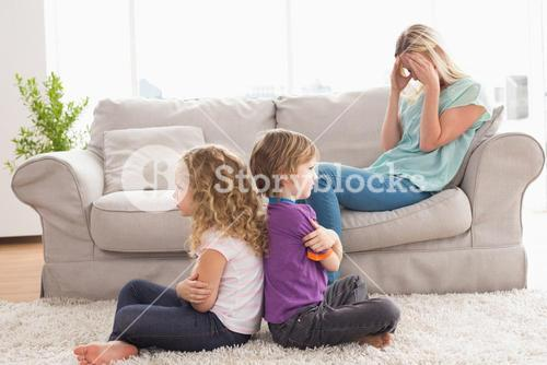 Angry siblings sitting arms crossed with upset mother on sofa