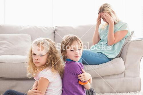 Angry siblings sitting arms crossed with sad mother on sofa