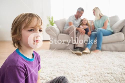 Upset boy sitting on floor while parents enjoying with sister