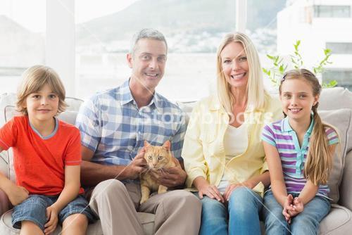 Portrait of happy family sitting with cat on sofa